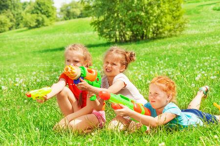 Three beautiful girls playing on a grass photo