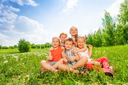 Five children sit together on a meadow photo