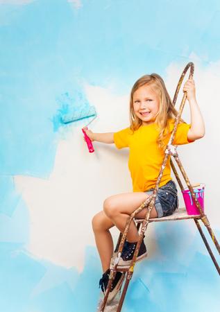 Little girl sits on a metal ladder 版權商用圖片