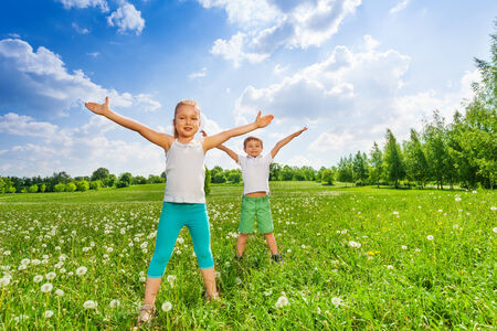 Two kids doing outdoor gymnastics on the grass photo