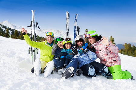 Smiling friends after skiing sitting on snow Stock Photo