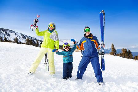 Positive parents in ski masks hold hands of son photo
