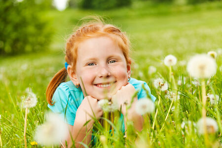 Pretty little girl lays on a grass photo