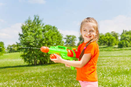 Nice girl playing with water gun photo