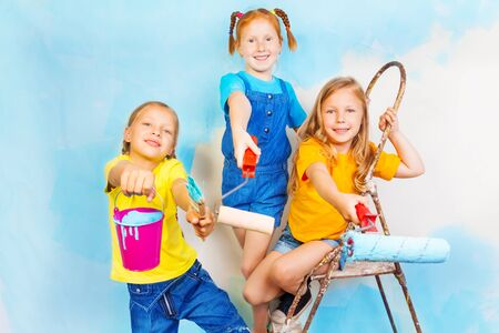 paint bucket: Three little girls smile on a background of wall