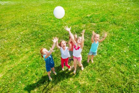 Kinderen spelen met een bal op een weide