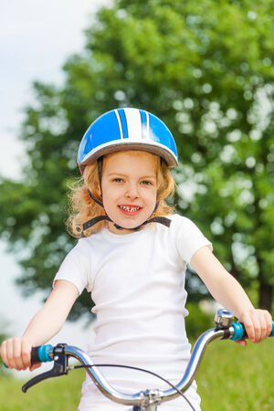 Little girl in a white shirt with bicycle photo