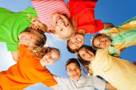 Happy kids close in circle on sky background Banque d'images