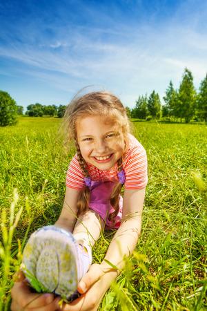 splitting up: Smiling girl making leg-split on grass in summer