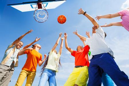 divertirsi: Bambini che giocano a basket con una palla su in cielo Archivio Fotografico