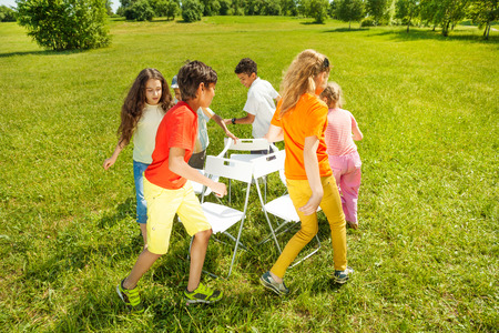 round chairs: Kids run around playing musical chairs game