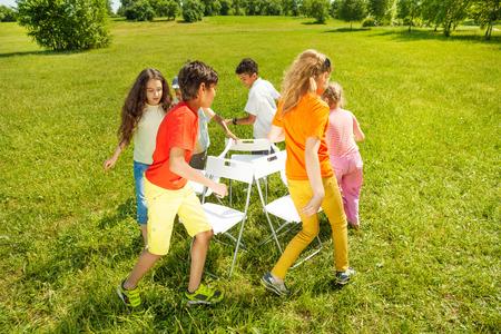 round chairs: Kids run around playing musical chairs game