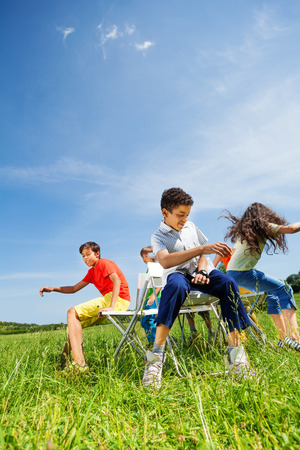 sit: Kids playing game and sit fast on chairs outside