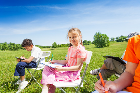 people sitting on chair: Kids holding sketch-boards and sit on chairs