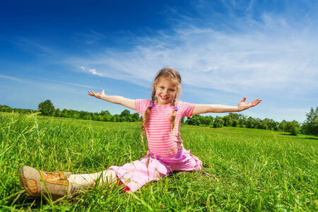 splitting up: Girl makes leg-split on grass with arms apart