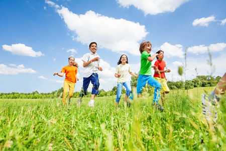 personas corriendo: Niños positivos jugando y corriendo en el campo