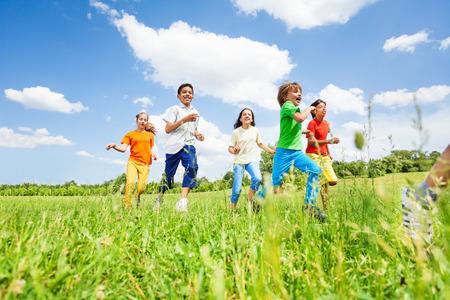 Positieve kinderen spelen en lopen op het gebied