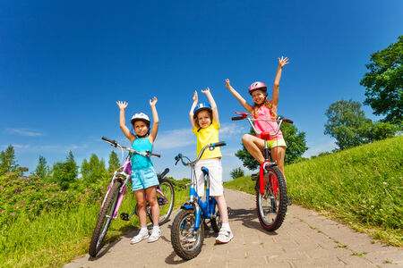 outsides: Three little girls on a bikes outsides
