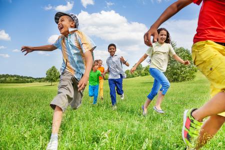 Kids in beweging van het lopen op groen veld