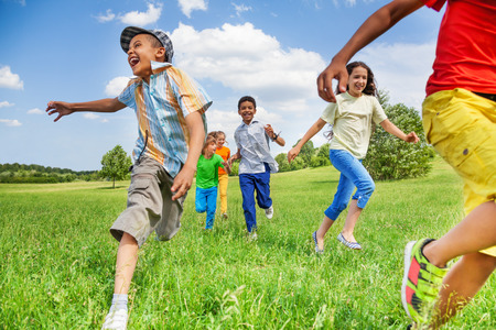 Kids in motion of running on green field