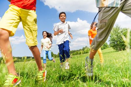 ni�os sonriendo: Ejecuci�n de ni�os juntos jugando fuera Foto de archivo