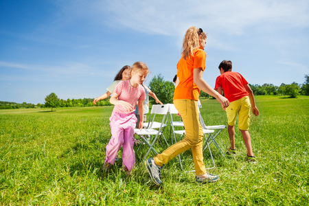 Children run around chairs playing a game outside Foto de archivo