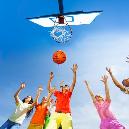 baloncesto chica: Niños que juegan a baloncesto vista desde abajo