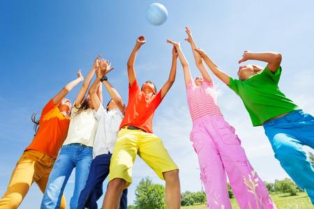 balon de voley: Felices los niños jugando con la pelota saltando en el aire