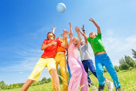 volleyball ball: Niños felices que juegan y que cogen la bola Foto de archivo
