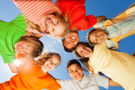 Happy children close in circle on sky background Stock Photo