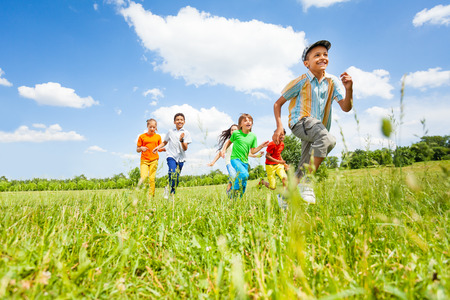 Happy kids playing and running in the field