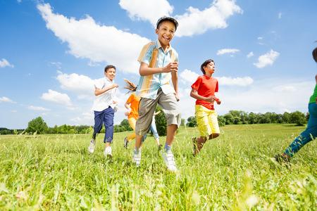 ni�as jugando: Ni�os positivos jugando y corriendo fuera