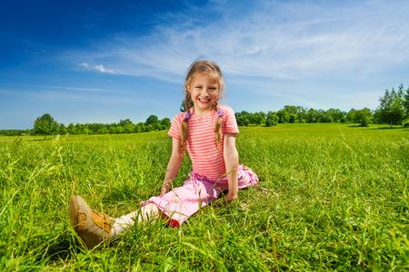 legs apart: Muchacha que estira las piernas abiertas sobre la hierba