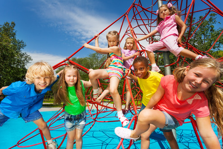 eight years old: Happy group of kids on red ropes together in park Stock Photo