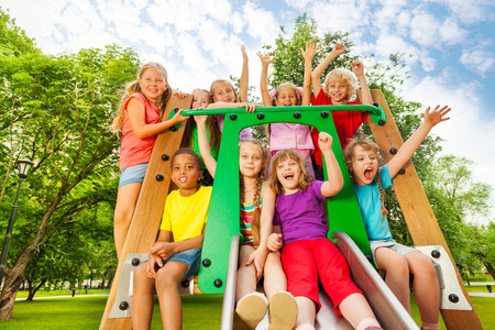 Excited kids on playground chute with arms up photo