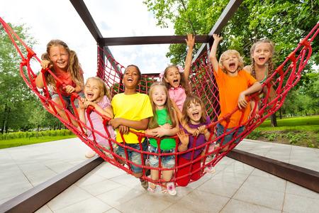 niños en area de juegos: Grupo de niños sentados en cuerdas de red de recreo
