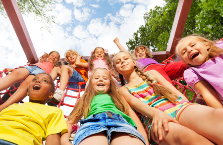 eight years old: View from below of happy kids on net ropes Stock Photo