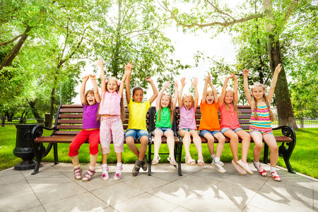 Excited kids with arms and sit in row on bench Stock fotó