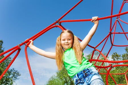 Girl with straight hands holds red rope of net photo