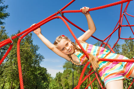 hangs: Girl with two braids hangs on ropes of red net Stock Photo