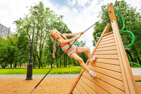 Girl with braids climbs on wooden construction photo