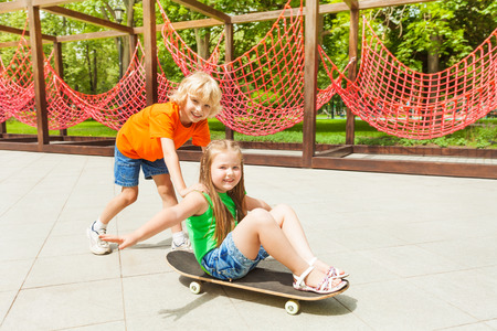Boy pushes girl on skateboard with arms apart photo