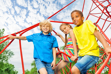 seven years: Two boys and girl sit on red ropes of playground Stock Photo