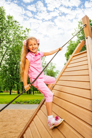 Happy girl climbs on wooden construction photo