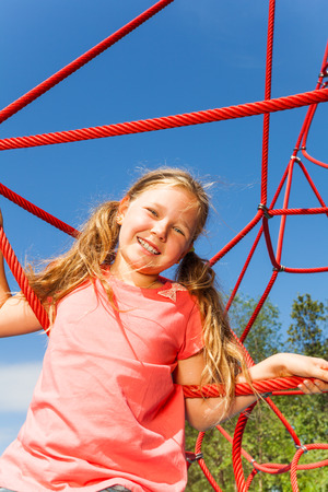 meshwork: Portrait of blond smiling girl on net ropes Stock Photo