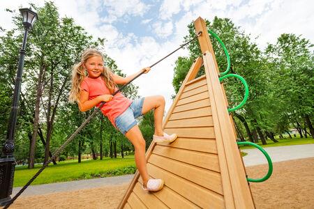 Active girl climbs on wooden construction photo