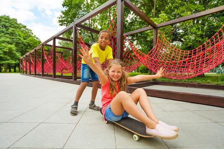 Boy pushing girl sitting on skateboard and roll photo
