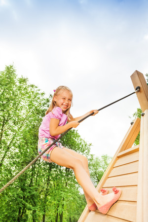 Smiling girl climbs on wooden construction photo