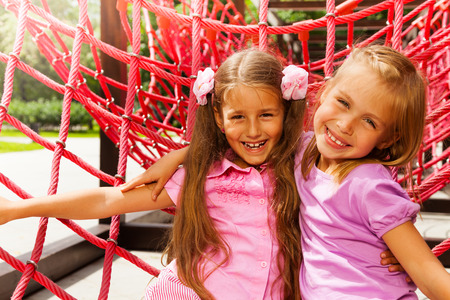 eight years old: Two pretty girls hugging on rope of playground