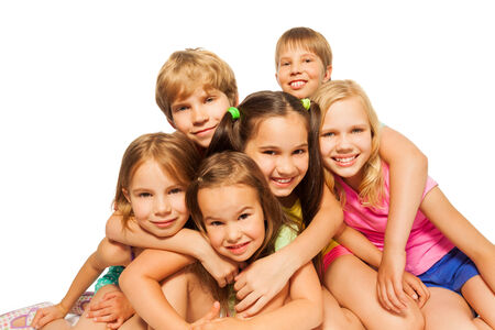 Six children sit hugging together photo